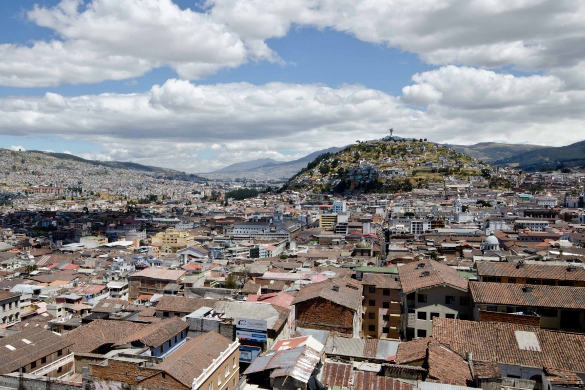 The city of Quito, Ecuador with roofs in the foreground, the Panecillo (a rounded top) in the background and blue skies
