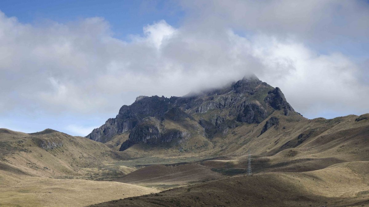 Paramo slopes call attention to to the rocky peak called Rucu Pichincha, which lies beneath a partially cloudy blue sky