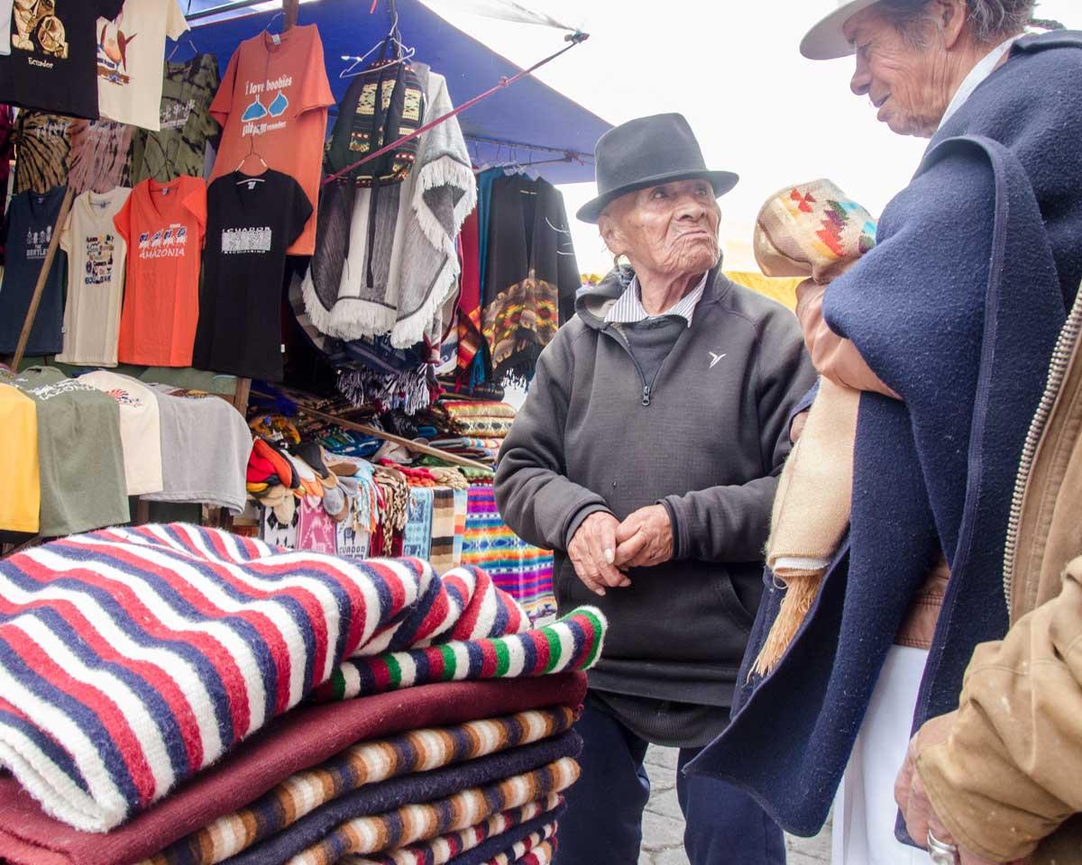 Poncho Vendor, Plaza de los Ponchos, Otavalo, Ecuador   ©Angela Drake