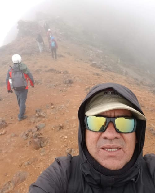 A selfie of author with the road and other hikers in the background on foggy path