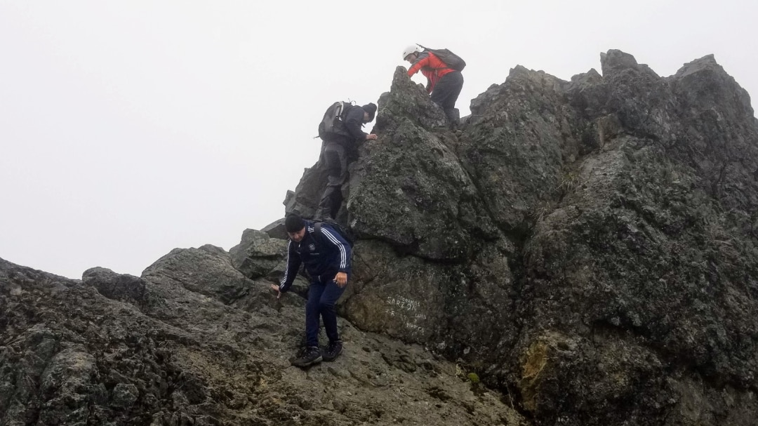 One hiker helps another climb to the top of Rucu Pichincha