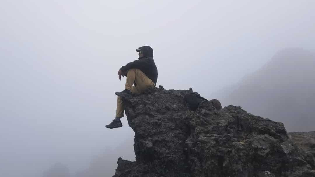 The author sitting at the tip of a ridge overlooking the fog